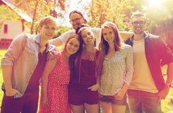 Amigos adolescentes felices que abrazan en el jardín del verano Fotos de archivo