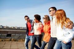 Amigos adolescentes felices que caminan a lo largo de la calle de la ciudad Foto de archivo