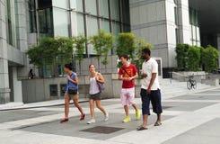 Amigos adolescentes felices que caminan a lo largo de la calle de la ciudad foto de archivo libre de regalías