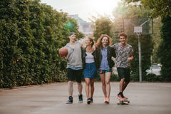 Amigos adolescentes felices que gozan en la cancha de básquet Fotografía de archivo