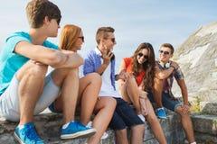 Amigos adolescentes felices que hablan al aire libre Foto de archivo
