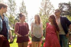 Amigos adolescentes felices que hablan en el jardín del verano Fotos de archivo libres de regalías