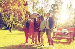 Amigos adolescentes felices que hablan en el jardín del verano Imagen de archivo libre de regalías