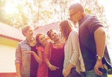 Amigos adolescentes felices que hablan en el jardín del verano Foto de archivo libre de regalías