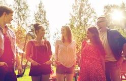 Amigos adolescentes felices que hablan en el jardín del verano Imagenes de archivo