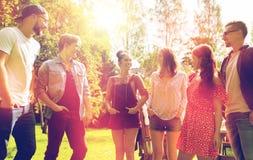Amigos adolescentes felices que hablan en el jardín del verano Foto de archivo