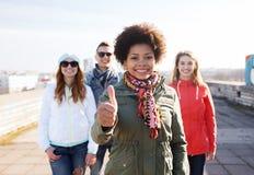 Amigos adolescentes felices que muestran los pulgares para arriba en la calle Foto de archivo