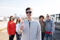 Amigos adolescentes felices que muestran los pulgares para arriba en la calle Fotos de archivo libres de regalías