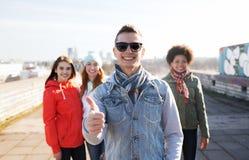 Amigos adolescentes felices que muestran los pulgares para arriba en la calle Imágenes de archivo libres de regalías