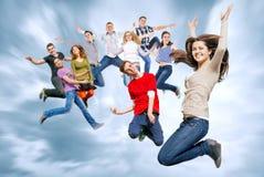 Amigos adolescentes felices que saltan en el cielo Imagen de archivo libre de regalías
