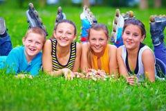 Amigos adolescentes felices que se divierten en parque de la primavera Imagen de archivo libre de regalías