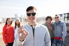 Amigos adolescentes felizes que mostram o sinal aprovado na rua Foto de Stock