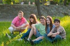 Amigos adolescentes felizes que têm o divertimento no parque Fotografia de Stock Royalty Free