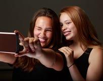 Amigos adolescentes femeninos en el estudio que toma un selfie Fotografía de archivo libre de regalías