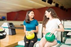 Amigos adolescentes femeninos que se divierten en una bolera Foto de archivo