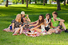 Amigos adolescentes jovenes que meriendan en el campo en el parque Imágenes de archivo libres de regalías
