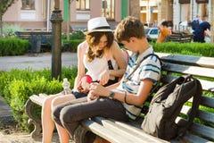 Amigos adolescentes muchacha y muchacho que se sientan en el banco en la ciudad, hablando Amistad y concepto de la gente Fotos de archivo libres de regalías
