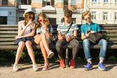 Amigos adolescentes muchacha y muchacho que se sientan en el banco en la ciudad, hablando Amistad y concepto de la gente Foto de archivo libre de regalías