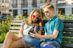 Amigos adolescentes muchacha y muchacho que se sientan en el banco en la ciudad, hablando Amistad y concepto de la gente Fotografía de archivo libre de regalías