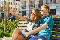 Amigos adolescentes muchacha y muchacho que se sientan en el banco en la ciudad, hablando, mirando en el teléfono, haciendo la fo Imágenes de archivo libres de regalías