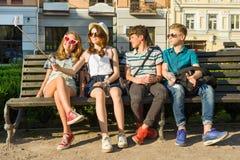 Amigos adolescentes muchacha y muchacho que se sientan en el banco en la ciudad, hablando, mirando en el teléfono, haciendo la fo Foto de archivo