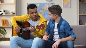Amigos adolescentes multirraciais que preparam-se para a competição que joga a carreira do músico da guitarra video estoque