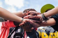 Amigos adolescentes multirraciales que se unen a las manos juntas en la cooperación Imágenes de archivo libres de regalías