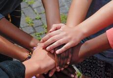 Amigos adolescentes multirraciales que se unen a las manos juntas en la cooperación Imagen de archivo libre de regalías