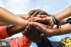 Amigos adolescentes multirraciales que se unen a las manos juntas en la cooperación Foto de archivo libre de regalías