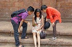 Amigos adolescentes profundamente que miran Smartphone Imágenes de archivo libres de regalías