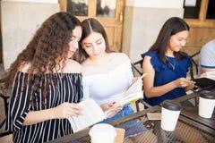 Amigos adolescentes que apreciam livros de leitura no café foto de stock
