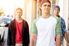 Amigos adolescentes que caminan en la calle Imagen de archivo libre de regalías