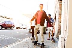 Amigos adolescentes que caminan en la calle con los monopatines Fotos de archivo libres de regalías