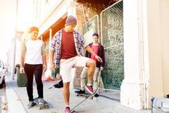 Amigos adolescentes que caminan en la calle con los monopatines Fotografía de archivo libre de regalías