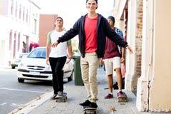 Amigos adolescentes que caminan en la calle con los monopatines Foto de archivo libre de regalías