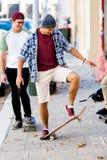 Amigos adolescentes que caminan en la calle con los monopatines Foto de archivo