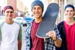 Amigos adolescentes que caminan en la calle con los monopatines Imagen de archivo libre de regalías