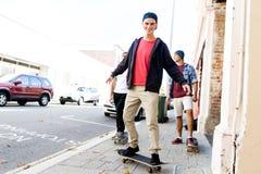 Amigos adolescentes que caminan en la calle con los monopatines Fotografía de archivo