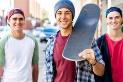 Amigos adolescentes que caminan en la calle con los monopatines Imagenes de archivo