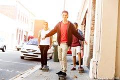 Amigos adolescentes que caminan en la calle con los monopatines Imagen de archivo