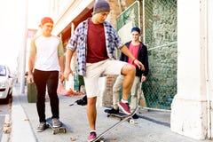 Amigos adolescentes que caminan en la calle con los monopatines Imágenes de archivo libres de regalías