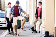 Amigos adolescentes que caminan en la calle con los monopatines Fotos de archivo