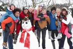 Amigos adolescentes que construyen el muñeco de nieve Fotografía de archivo libre de regalías