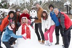 Amigos adolescentes que construyen el muñeco de nieve en jardín Fotos de archivo libres de regalías
