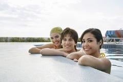 Amigos adolescentes que descansan en The Edge de la piscina Fotos de archivo libres de regalías