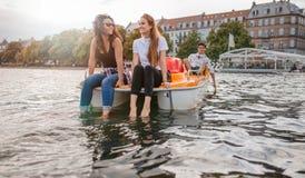 Amigos adolescentes que disfrutan de canotaje en el lago Imagen de archivo libre de regalías