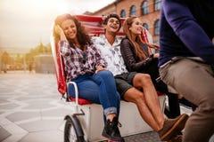 Amigos adolescentes que disfrutan de paseo del triciclo Imagen de archivo libre de regalías