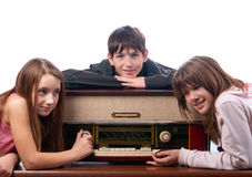 Amigos adolescentes que escuchan la música en radio vieja Fotografía de archivo