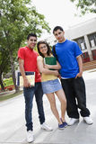 Amigos adolescentes que estão em Front Of School Fotos de Stock Royalty Free