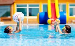 Amigos adolescentes que juegan con la bola en la piscina Imagen de archivo libre de regalías